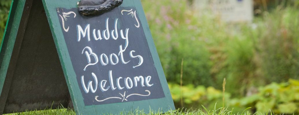 Muddy boots welcome sign