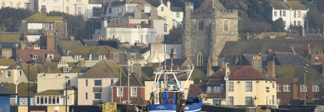 Fishing trawler, seafront houses with church