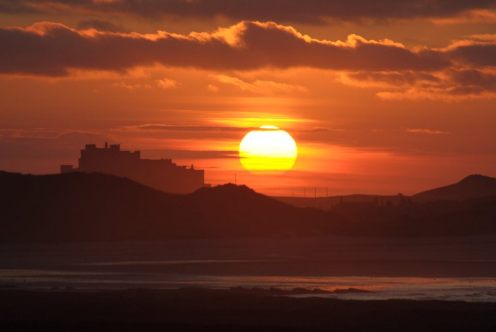 Sun setting over Bamburgh Castle